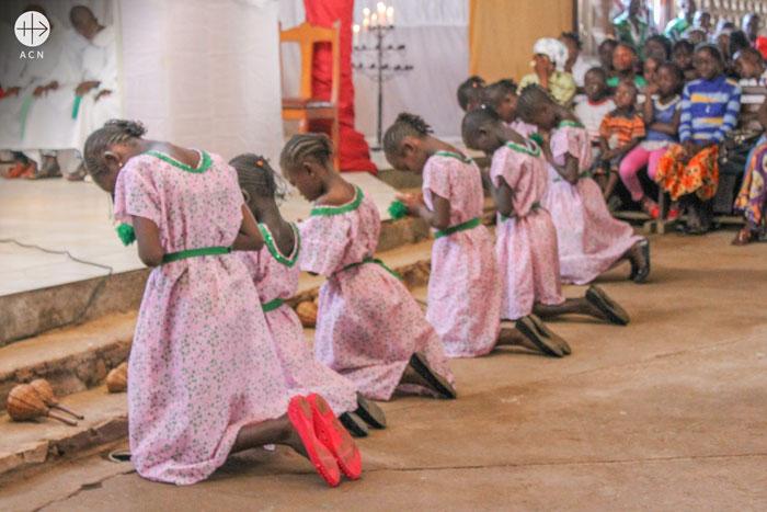 Central African Republic. Girls praying in St Joseph Mukasa parish during Holy Mass