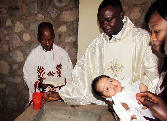 Father Apollinaire Cibaka Cikongo is baptizing a little child during holy mass
