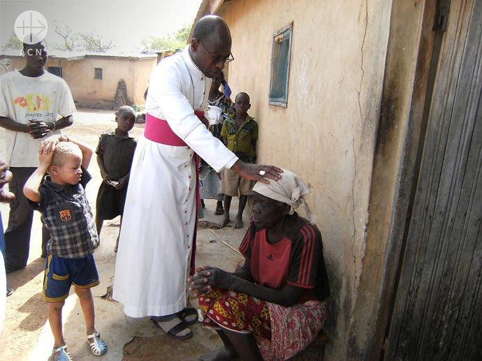 Bishop Ignace Bessi Dogbo blesses the old lady in Ivory Coast