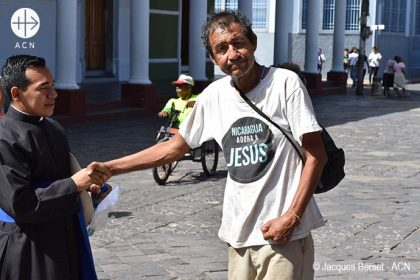 "Mgr Jorge Solórzano Pérez, Bishop of Granada, during the distribution of a meal for the poor of the city - Poor man wearing a T-Shirt with the slogan ""Nicaragua loves Jesus""."