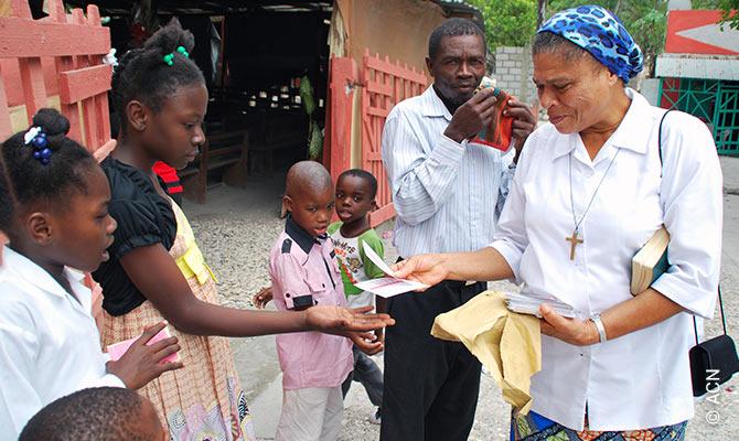 Une soeur de la paroisse de Bainet distribue a des enfants des cartes qui ont ete ecrites et envoyees de France par des donateurs de l'ACN.