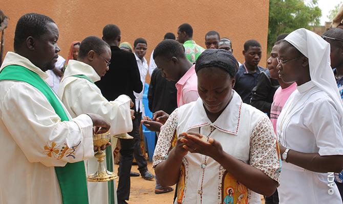 Heilige Kommunion in einem Camp, wo junge Christen und Muslime zusammenleben.