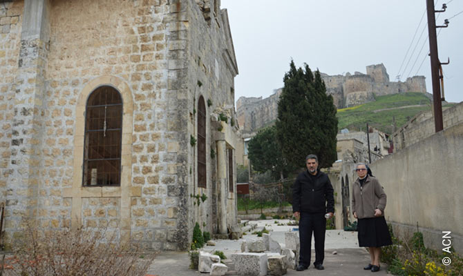 Church of the Assumption of Our Lady, in the town of Qal'at Al Hosn (Husn Haret Saray/ Haret Sary in Al-Husn), next to the Krak des Chevaliers fort. In the picture appears, Fr. George Maamary, parish priest and Sister Catherine Battikha, nun of Our Lady of Perpetual Help in Marmarita.