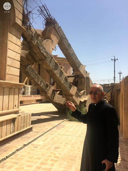 Syriac Catholic parish priest Father Georges Jahola in front of the bell tower ISIS destroyed.
