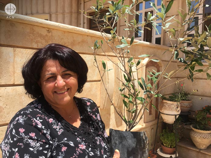 Rabah with her Olive tree received by ACN