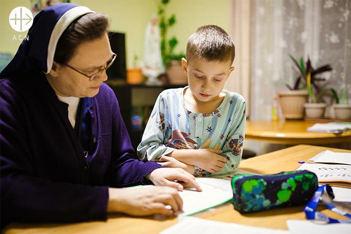 Sister Wiera Zinkowska doing homework with children.