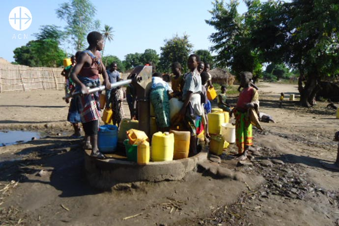 Women and children getting water at a water pump.