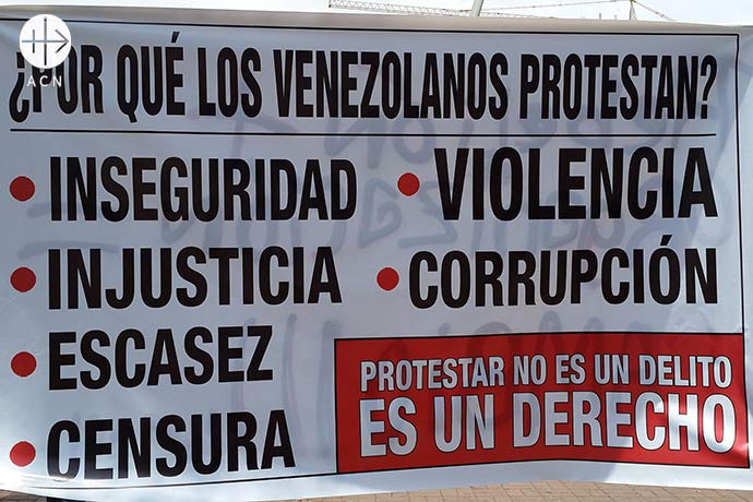 """A poster explaining why the opposition protest. """"Why do the Venezuelans protest? Insecurity, injustice, shortages, censorship, violence, corruption. Protesting is not a crime. Is a right""""."""