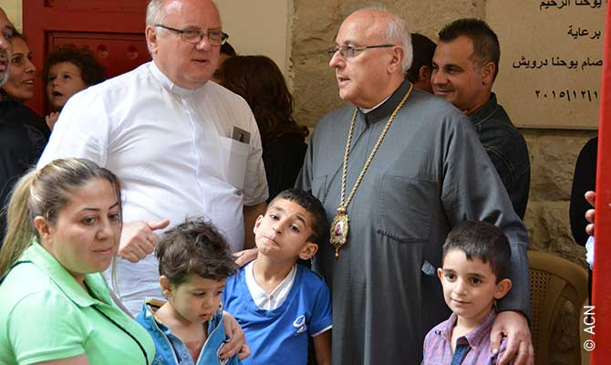 """Melkite Greek Catholic Archbishop Issam John Darwish of Furzol Zahle and the Bekka and Fr Andrzej Halemba, ACN's Middle East expert, with Syrian refugees at the ACN sponsored """"Saint John the Merciful Table"""" – a humanitarian feeding program in Zahle."""