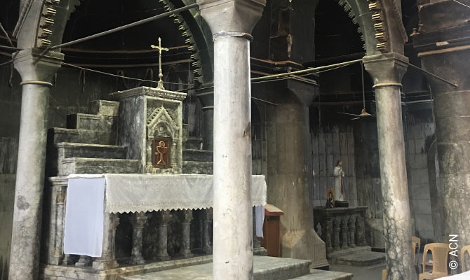 The Divine Liturgy in Al-Tahira Cathedral – the walls still blackened and partly open to the elements.