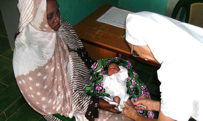 Missionsschwester Hilda vom Franziskanerorden in einer Klinik mit einem Neugeborenen.