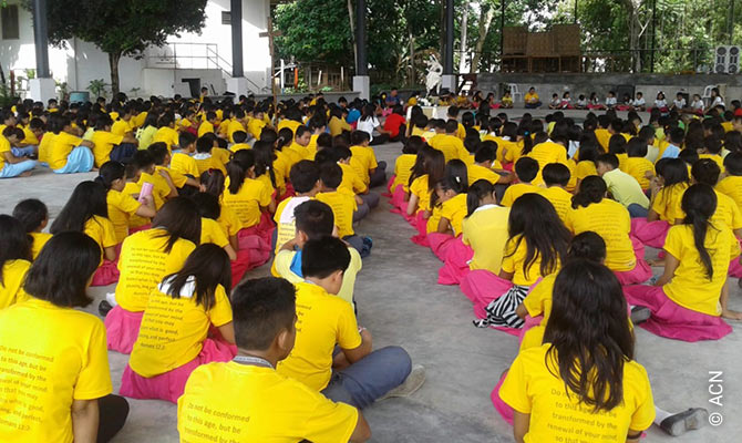 Schoolchildren in Tibungco, Davao City, praying the rosary.