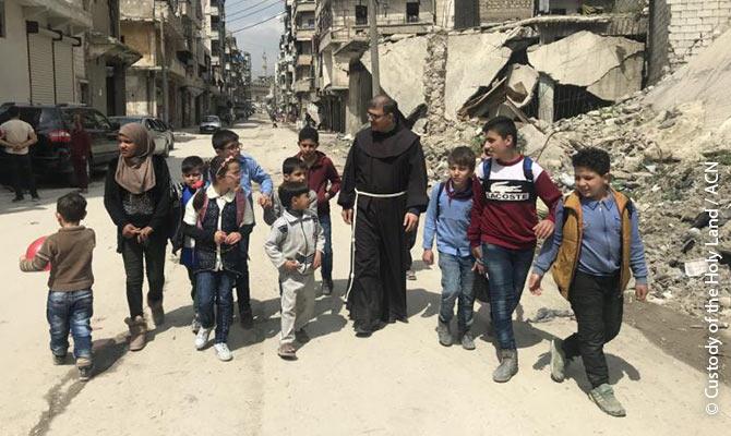 Padre Firas Lutfi con dei bambini ad Aleppo.