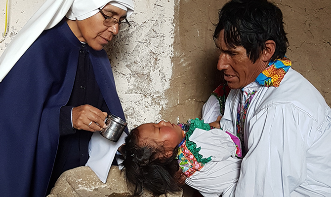 """A missionary religious sister of the congre-gation """"Misioneras de Jesús Verbo y Víctima"""" at a baptism in Sucre."""