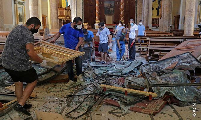 Jovens voluntários cristãos ajudam a limpar a catedral maronita danificada.