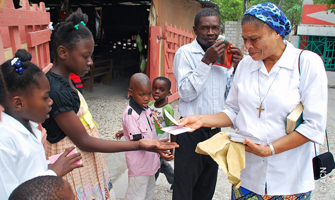 A sister in Bainet parish distributes cards written by French ACN donors to children.