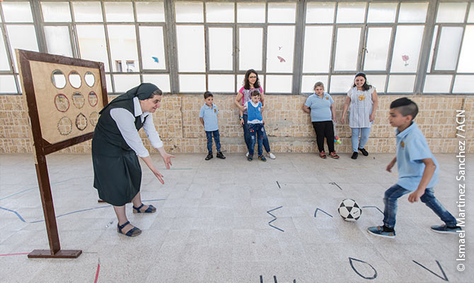 "Sister Samia of the Sisters of the Sacred Hearts of Jesus and Mary in Homs playing football with one of the children of ""Le Sénevé"", a centre that cares for 80 children with disabilities or autism.."
