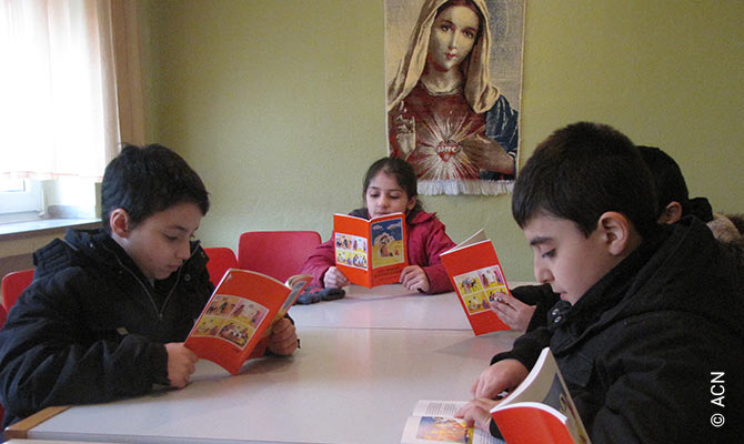 Iraqi refugee children reading the children's Bible in the Chaldean Catholic community in Essen/Germany. The community was provided with 300 Arabic Bibles.