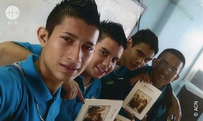 """Jovens nas Honduras recebem o """"Pequeno Catecismo Catolico""""."""