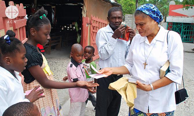 Una suora nella parrocchia Bainet distribuisce ai bambini le cartoline scritte dai donatori dell'ACN in Francia.