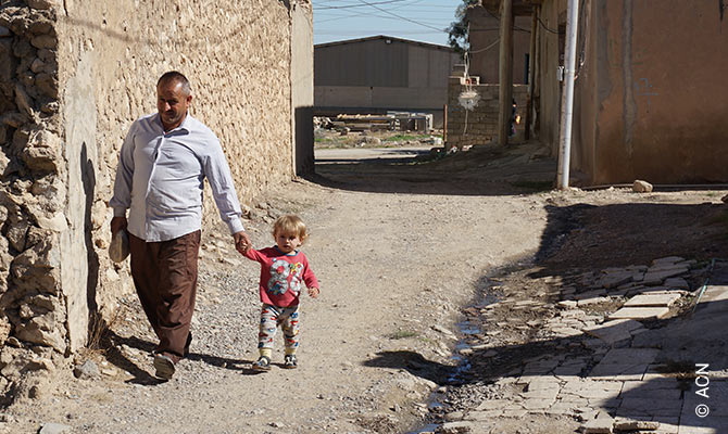 A man and a child in Batnaya, a town that has also suffered extensive war damage.